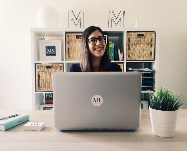 Escritório com uma Especialista em Excel em frente a um computador, com uma agenda e cartões de visita da empresa