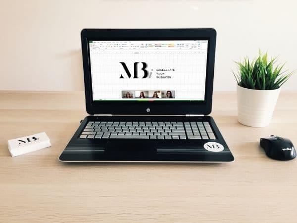 Portátil com uma formação de Excel a decorrer online com 3 formandos. Secretária com uma planta, rato e cartões de visita da empresa.