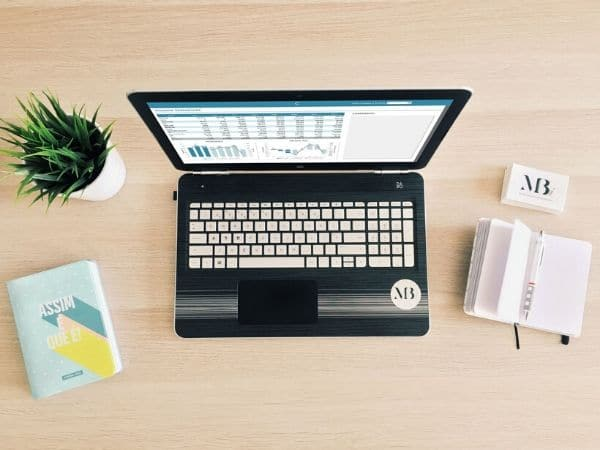 Secretária com um portátil com um exemplo de um Modelo Financeiro desenvolvido inteiramente em Excel, uma agenda, um bloco de notas e cartões de visita da empresa