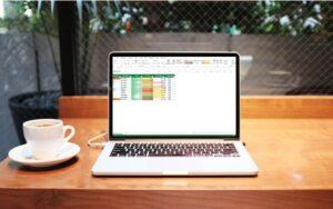 Secretária com computador com Excel com uma tabela personalizada com formatação condicional